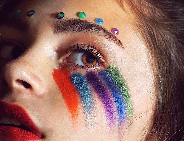 Girl with rainbow painted makeup around her eye.