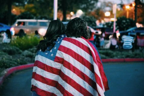 Two people draped in an American flag.