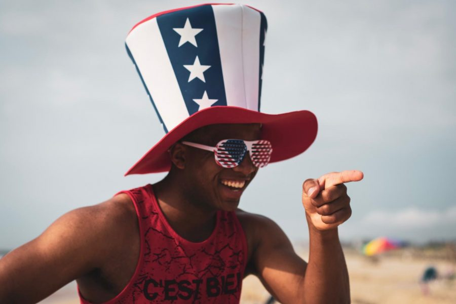Person on the beach wearing an American flag hat.