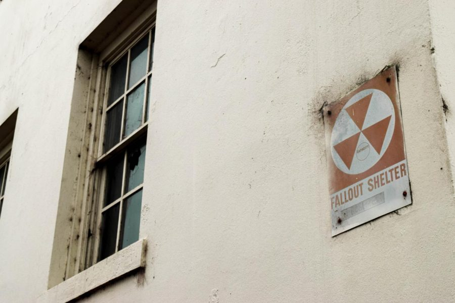 Image of a 'Fallout Shelter' sign on the side of a damaged building.