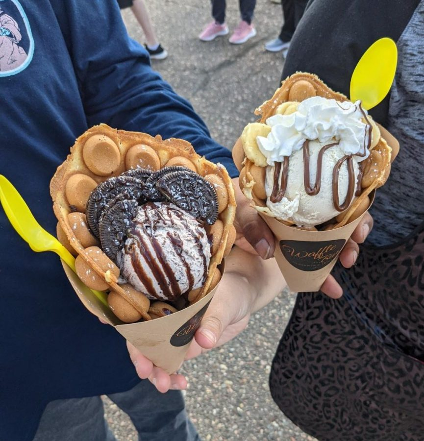 Two Waffle Bar, waffle cone sundaes held by students in line.