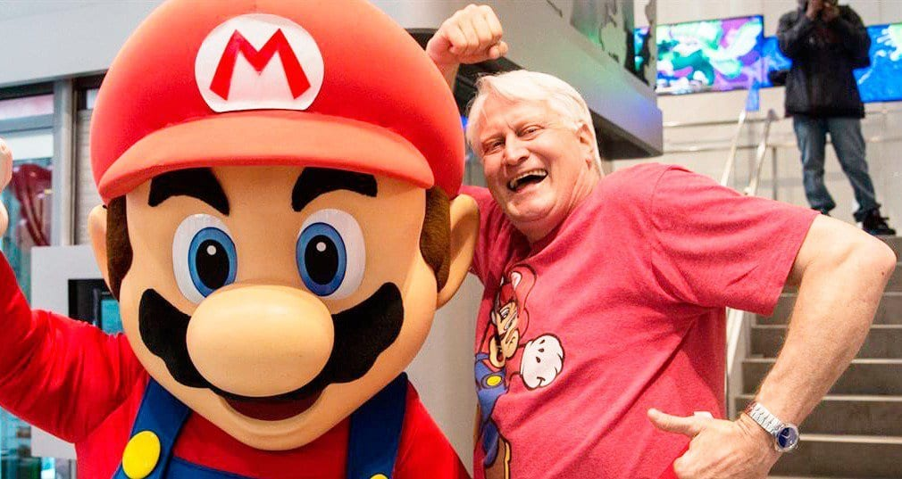 Charles Martinet, the voice of Mario in the animated upcoming movie, standing with Mario Mascot at a promotional event.