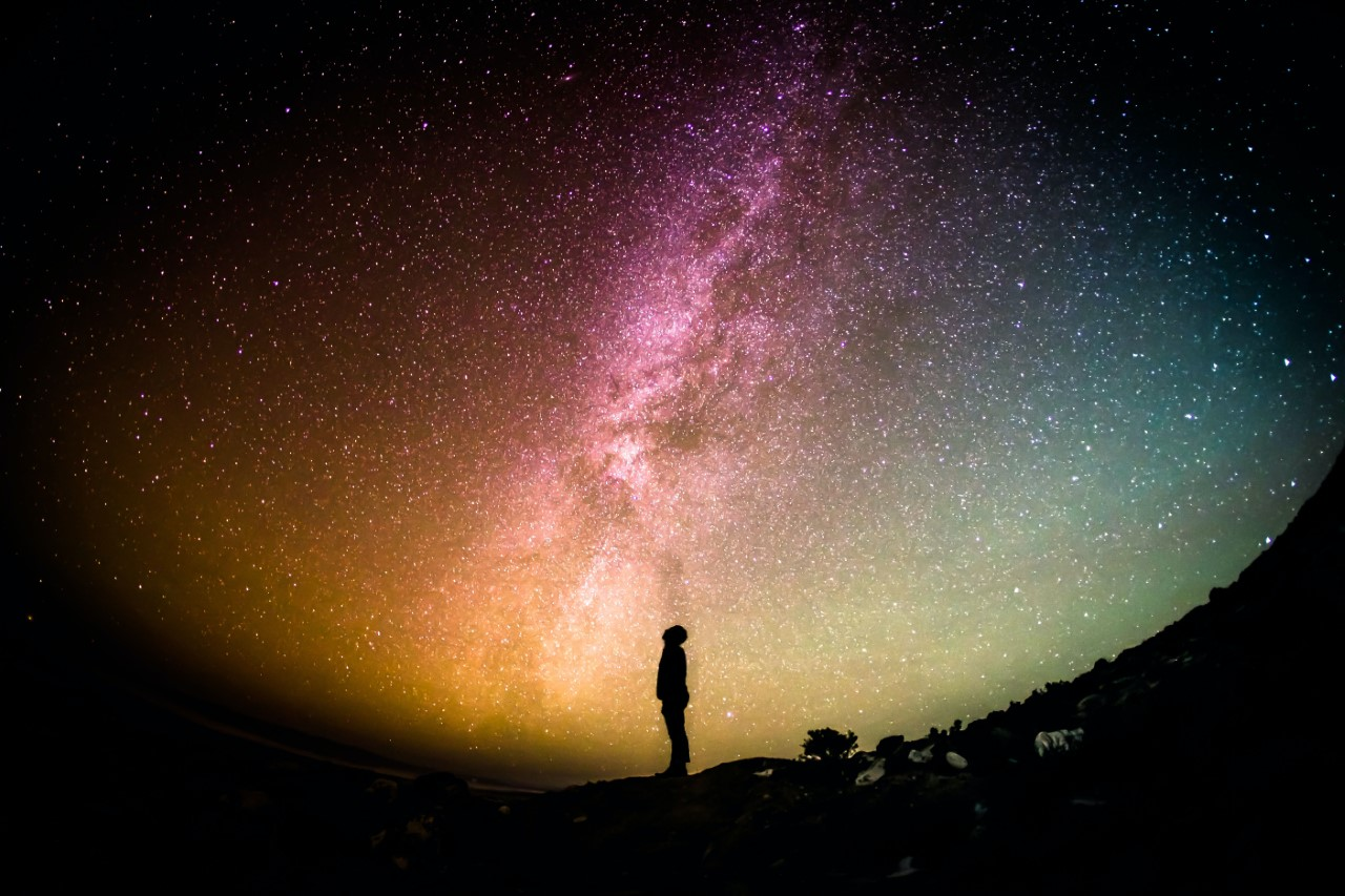Silhouette of person looking into space gazing at the stars.